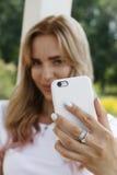 Junges Mädchen im Weiß macht selfie Lizenzfreie Stockfotografie