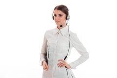 Junges Mädchen im weißen Hemd und in den Kopfhörern mit Mikrofon hält seine Hand auf der Seite und blickt in Richtung Lizenzfreies Stockfoto