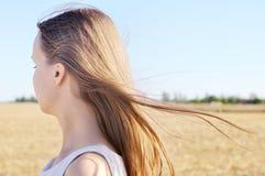 Junges Mädchen im weißen Kleid steht auf dem Gebiet und Wind flattert ihr Haar Lizenzfreies Stockfoto