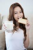 Junges Mädchen isst den neuen Toast, der ein Glas Milch hält lizenzfreies stockbild