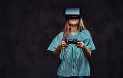 Junges Mädchen kleidete zufälliges, das Spiel mit den Steuerknüppel und Gläsern der virtuellen Realität spielend auf der Dunkelhe stockfotos