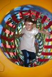 Junges Mädchen klettert durch netzförmigen Tunnel in der weichen Spielmitte Stockfotografie