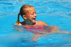 Junges Mädchen lacht im Swimmingpool Lizenzfreie Stockfotos