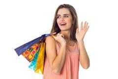 Junges Mädchen lacht und blickt in Richtung des Haltens von den farbigen Taschen, die auf weißem Hintergrund lokalisiert werden Stockfoto