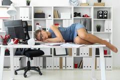 Junges Mädchen liegt mit geschlossenen Augen auf Dokumenten auf Schreibtisch im Büro stockfotografie