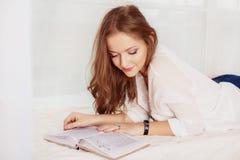 Junges Mädchen liegt und liest das Buch Das Konzept der Freizeit und des L lizenzfreie stockbilder