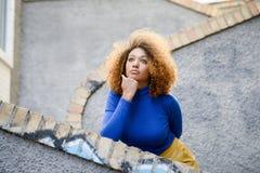 Junges Mädchen mit Afrofrisur im städtischen Hintergrund lizenzfreie stockfotos