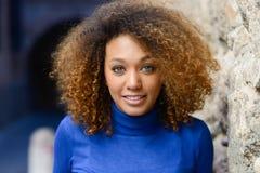 Junges Mädchen mit Afrofrisur lächelnd im städtischen Hintergrund stockfoto