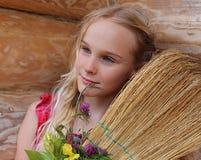 Junges Mädchen mit Besen und Blumen Stockfoto