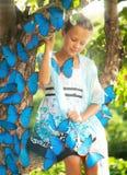 Junges Mädchen mit blauen Schmetterlingen Stockbilder