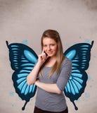 Junges Mädchen mit blauer Illustration des Schmetterlinges auf der Rückseite Stockbilder