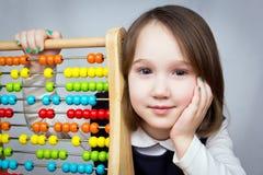 Junges Mädchen mit dem Abakus, der Kamera betrachtet Lizenzfreie Stockbilder