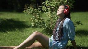 Junges Mädchen mit dem dunklen Haar hörend Musik auf Kopfhörern unter Verwendung einer Tablette, die auf dem Gras im Park hat ein stock video footage