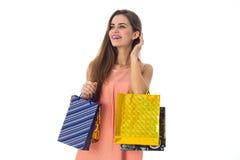 Junges Mädchen mit dem Einkaufen blickt in Richtung lokalisiert auf weißem Hintergrund Stockbilder