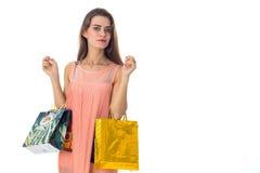 Junges Mädchen mit dem Einkaufen in den Händen blickt in Richtung lokalisiert auf weißem Hintergrund Stockbilder