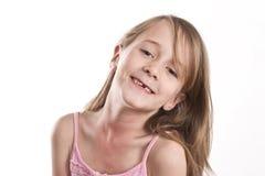 Junges Mädchen mit dem fehlenden Zahn, mit einem netten Lächeln und einem Achselzucken Lizenzfreie Stockbilder