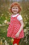 Junges Mädchen mit dem gelockten roten Haar auf dem Gebiet von Wildflowers Lizenzfreie Stockfotos