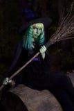 Junges Mädchen mit dem grünem Haar und Besen in der Klage der Hexe in Wald-Halloween-Zeit Stockfoto