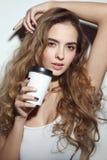 Junges Mädchen mit dem langem gelockten Haar und Tasse Kaffee in h lizenzfreies stockbild