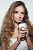 Junges Mädchen mit dem langem gelockten Haar und Tasse Kaffee in h lizenzfreies stockfoto