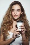 Junges Mädchen mit dem langem gelockten Haar und Tasse Kaffee in h lizenzfreie stockfotos