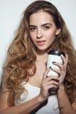 Junges Mädchen mit dem langem gelockten Haar und Tasse Kaffee in h lizenzfreie stockbilder
