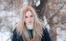 Junges Mädchen mit dem langen blonden Haar auf einem unscharfen Hintergrund eines Parks des verschneiten Winters lizenzfreies stockbild