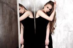 Junges Mädchen mit dem langen schönen Haar und rauchigen den Augen, die das schwarze Maxi Abendkleid aufwirft mit einem Spiegel t Lizenzfreie Stockfotos