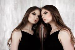 Junges Mädchen mit dem langen schönen Haar und rauchigen den Augen, die das schwarze Maxi Abendkleid aufwirft mit einem Spiegel t Lizenzfreies Stockbild