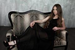 Junges Mädchen mit dem langen schönen Haar und rauchigen den Augen, die schwarzes Maxi Abendkleid tragen Schönes Tanzen der junge Stockbild