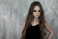 Junges Mädchen mit dem langen schönen Haar und rauchigen den Augen, die schwarzes Maxi Abendkleid tragen Schönes Tanzen der junge Lizenzfreie Stockfotografie