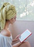 Junges Mädchen mit dem nassen Haar mit einer Schale, die Bilder schaut Stockfoto