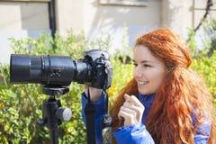 Junges Mädchen mit dem roten Haar fotografierend auf der Straße Stockbilder