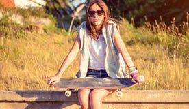 Junges Mädchen mit dem Skateboard, das über der Wand sitzt Stockfotos