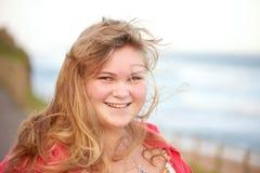 Junges Mädchen mit dem unordentlichen Haar, das im beschäftigten Lächeln des Winds an der Kamera durchbrennt Lizenzfreie Stockfotografie