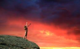 Junges Mädchen mit den angehobenen Händen auf Berg Stockfotografie