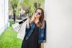 Junges Mädchen mit den Einkaufstaschen, die auf der Spalte sich lehnen Stockfotos