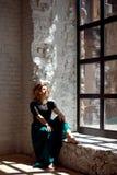 Junges Mädchen mit den geschlossenen Augen, die zu Hause nahe dem Fenster sitzen und warmes Sonnenlicht genießen Lizenzfreies Stockbild
