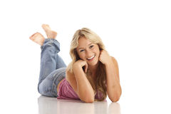 Junges Mädchen mit den Jeans, die auf Fußboden legen stockfotografie