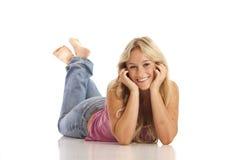Junges Mädchen mit den Jeans, die auf Fußboden legen lizenzfreie stockfotos