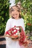 Junges Mädchen mit einem Blumenstrauß von Blumen von den Rosen lizenzfreie stockfotos