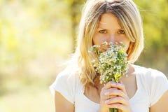 Junges Mädchen mit einem Blumenstrauß von Blumen in der Natur Stockbilder