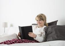 Junges Mädchen mit einem Buch, das in camera schaut Lizenzfreie Stockbilder