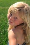Junges Mädchen mit einem Lächeln, das zurück schaut Lizenzfreie Stockfotografie