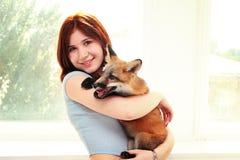Junges Mädchen mit einem Welpen des roten Fuchses Stockfotos