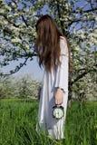 Junges Mädchen mit einer Alarmuhr in ihren Händen Lizenzfreie Stockfotos