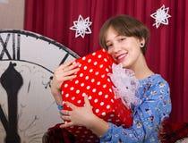 Junges Mädchen mit Geschenkbox auf dem Hintergrund der Stunden des neuen Jahres stockfotos