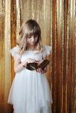 Junges Mädchen mit goldener Rose auf goldenem Hintergrund Stockfoto