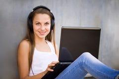 Junges Mädchen mit Kopfhörern und Notizbuch Lizenzfreies Stockfoto