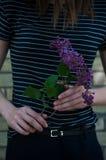 Junges Mädchen mit lila Blumen Stockfoto